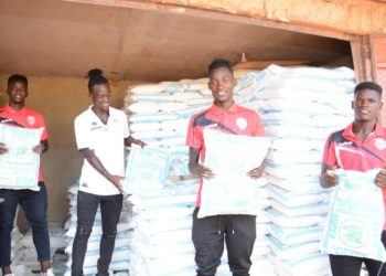 Express FC players including captain Disan Ggaliwango (2nd-left) pose with some of the food stuff from Betway Uganda on Wednesday. (PHOTO/Courtesy)