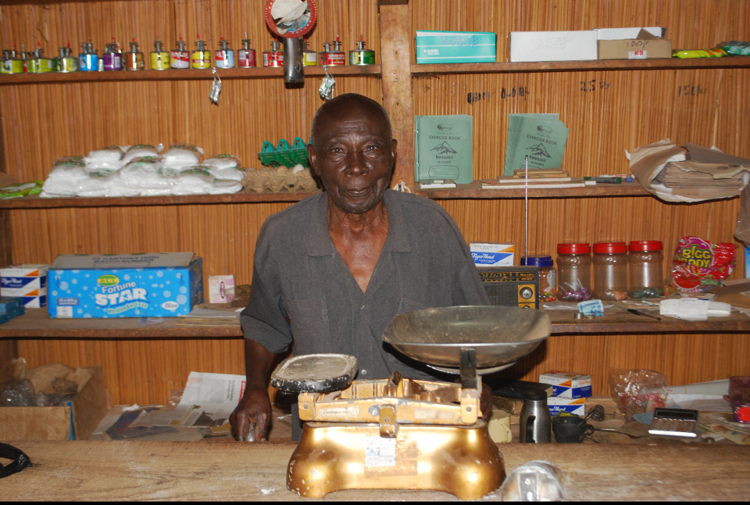 Mr Kolliabu Maswere in his shop and behind him is his radio set giving him entertianmeninformation (PHOTO/David Mafabi).
