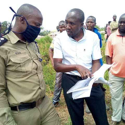 MP Nandala shows a police officer, the documents he has for the land in question.
