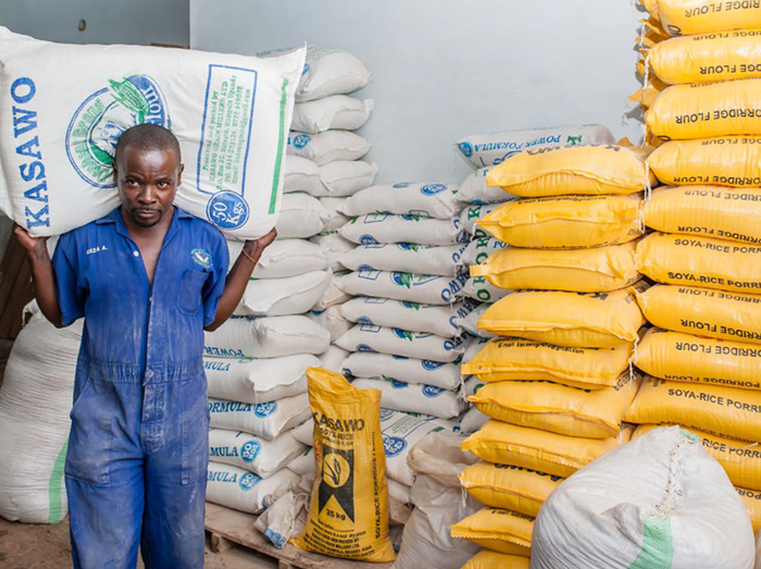 A maize flour store attendant carrying a bag for a customer.
