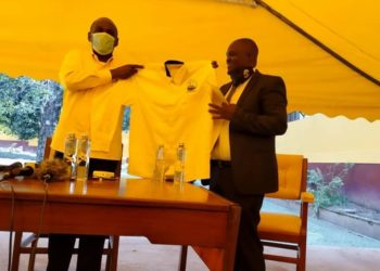 Yusuf Mutembuli, the Democratic Party Vice President in charge of the Eastern Region being given NRM attire (PHOTO/Courtesy).