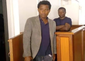 Ronald Muhumuziibwe and Francis Mutambuzi in the dock at the Anti-Corruption Court where they were charged with impersonating URA tax officer and fraud on Thursday (PHOTO/Courtesy).