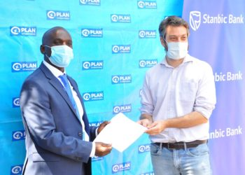Stanbic Bank Uganda Head of Personal Markets Israel Arinaitwe and Plan International's Head of Programmes Greg Lavendar after signing an MoU during the prepaid cards Handover ceremony (PHOTO/Courtesy).