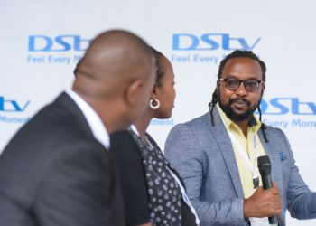 Mr. Colin Asiimwe, the Head of Marketing during the launch of Showmax at MultiChoice Uganda offices, looking on is Ms. Joan K. Semanda, the PR and Communications Manager and a staff at MultiChoice Uganda (PHOTO/Courtesy)