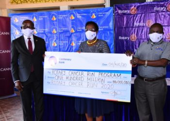 L-R Mr. Fabian Kasi, Managing Director Centenary Bank, handing over a dummy cheque worth Ush 100 million towards the 2020 Virtual Cancer Run to Ms. Rosetti Nabbumba Nayenga Rotary District Governor for Uganda and Tanzania, and Mr. Stephen Mwanje, Past District Governor. This was during the launch of the 2020 Virtual Cancer Run at Hotel Africana on Tuesday August 4, 2020 (PHOTO/Courtesy)