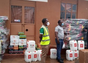 Bishop Naboth Tumuhairwe, the Director of Adullam Orphanage and Primary School receiving the consignment from the CCBA team led by the Mbarara Plant Manager Joackim Baluku (PHOTO/Courtesy).