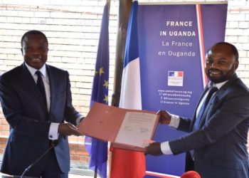 The French Ambassador to Uganda, H.E Jules - Armand Aniambossou and Thomas Mbusa Lekatamba the director of Bonjour Kampala display the MOU after signing at the French Embassy in Nakasero (PHOTO/ Abraham Mutalyebwa).