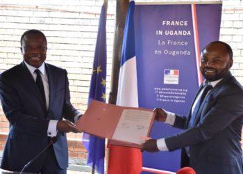 The French Ambassador to Uganda, H.E Jules - Armand Aniambossou and Thomas Mbusa Lekatamba the director of Bonjour Kampala display the MOU after signing at the French Embassy in Nakasero (PHOTO/ Abraham Mutalyebwa).