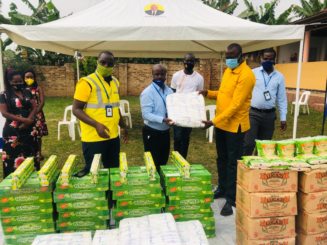 Roger Mugisha, Head of Corporate Affairs Letshego Uganda hands over Covid relief items to Proprietor of Kasolo Foundation Haruna Kasolo, MP Kyotera (PHOTO/Courtesy).