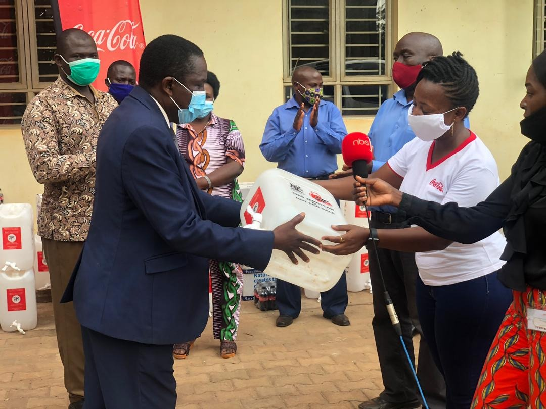 Kigongo Mathius, Chairman Buikwe District Taskforce receiving the jerrycan from Anita Natuha, Regional Trade Marketing Representative, Coca-Cola Beverages Africa (CCBA) in Uganda (PHOTO/Courtesy)