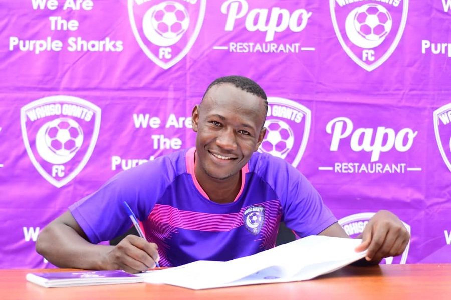 Masiko smiles for the camera while penning the three-year permanent deal with Wakiso Giants FC. (PHOTO/Courtesy)