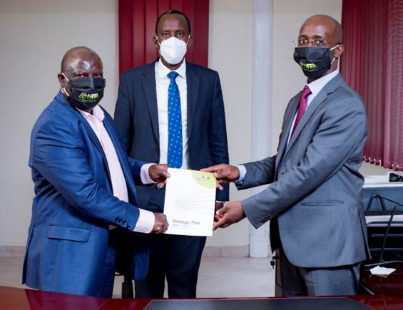 Outgoing NITA-U ED, James Saaka hands over the NITA-U strategic plan to new NITA ED, Hatwib Mugasa. Looking on is the NITA-U Board chair, John R Musinguzi (PHOTO/Courtesy).