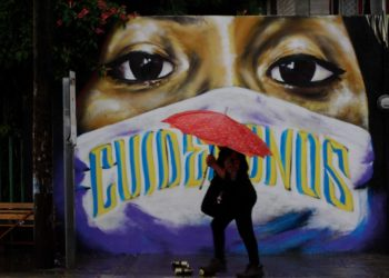 A woman passes a graffito reminding people to wear masks on a street in Tlaxcala, Mexico, Sept. 10, 2020. (Photo by Jesus Alvarado/Xinhua).