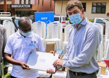 Mr Malinzi (left) receives the IT equipment contributed by WFP, from Mr Anderson. More IT equipment and cameras contributed by WFP are below