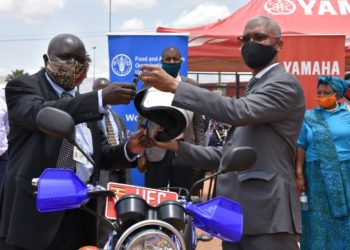 Stephen Koma, Assistant Commissioner in charge of District Inspection in the Ministry of Local Government receives keys for one of the motorcycles from  the FAO Country Representative in Uganda, Antonio Querido (PHOTO/G. Lugaaju).
