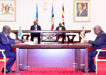 Presidents Tshisekedi and Museveni (in background) witness signing of memoranda of understanding on security, infrastructure and tourism by Uganda Foreign Affairs Minister, Sam Kutesa (right) and Congolese Deputy PM and Minister of Justice, Celestine Tunda ya Kasende (PHOTO/File).