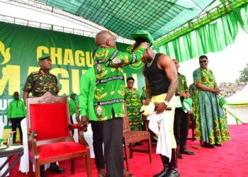 Singer Diamond Platinumz receiving a hat prize from Tanzania President Pombe Magefuli