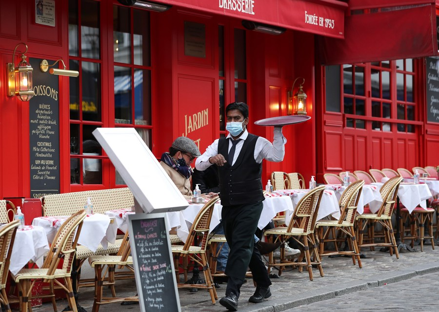 A waiter serves at the terrace of a restaurant at the Place du Tertre at the Montmartre, Paris, France, Oct. 28, 2020 (PHOTO/Xinhua).