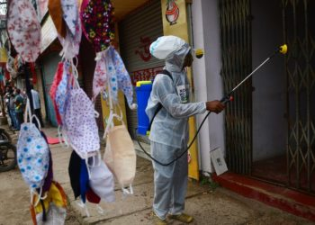 A worker sanitizes the door of a shop at a market in Agartala, the capital city of India's northeastern state of Tripura, Oct. 18, 2020. (PHOTO/Xinhua)
