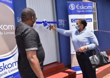Eskom Uganda Managing Director Thozama Gangi (R) cuts a ribbon to commission the renovated Administration block at Njeru Primary School. Looking on is School Board of Governors  Chairman, Fred Kiwanuka (PHOTO/Courtesy)