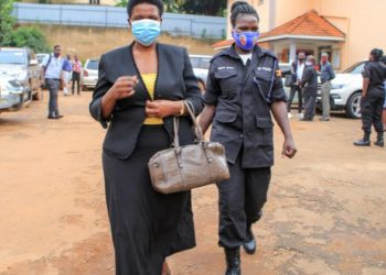 Ms Ntambi being led to a prison bus by a police officer (PHOTO/PML Daily).