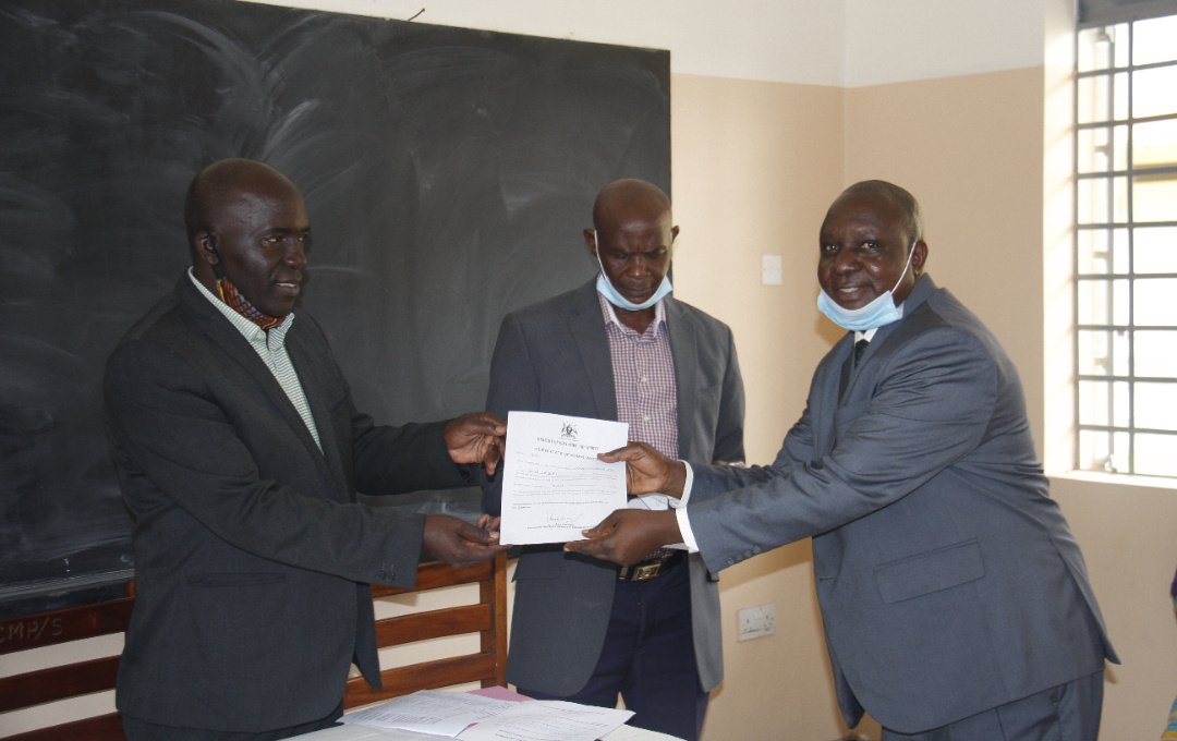 Entebbe Mayor Vincent Kayanja (L) hands over a certificate to Mr Stephen Nabende (R) Head Teacher Lake Victoria Primary School as P.E.O Mr moses Ndaga (M) observes (PHOTO/PML Daily).