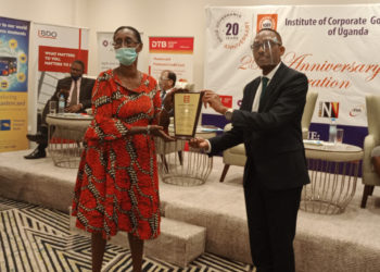 President ICGU Uganda, Michael Mugabi hands over a plaque to a member during the Institute's 20 year anniversary celebration (PHOTO/Courtesy).