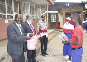 Entebbe Municipal Mayor Mr Vincent Kayanja hands over sanitisers to pupils of Kiwafu Muslim Primary School on Wednesday (PHOTO/PML Daily).