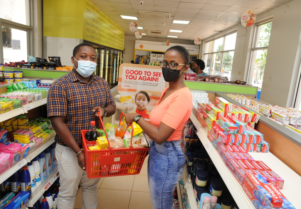 L-R: Mark Mutungi the Vivo Energy Fuels Brand Manager hands over grocery Items to Leyla Kyobutungi, one of the winners of Shell complimentary prizes. Over 3000 customers have been rewarded with prizes worth UGX 500M in the just concluded Good To See You Again Campaign (PHOTO/Courtesy).