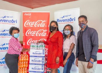 Anita Faith Natuha, Regional Trade Marketing Representative, Coca-Cola Beverages Africa handing over the drink consignment to Esther Birungi, Founder of Birungi Charities at Namanve (PHOTO/Courtesy).