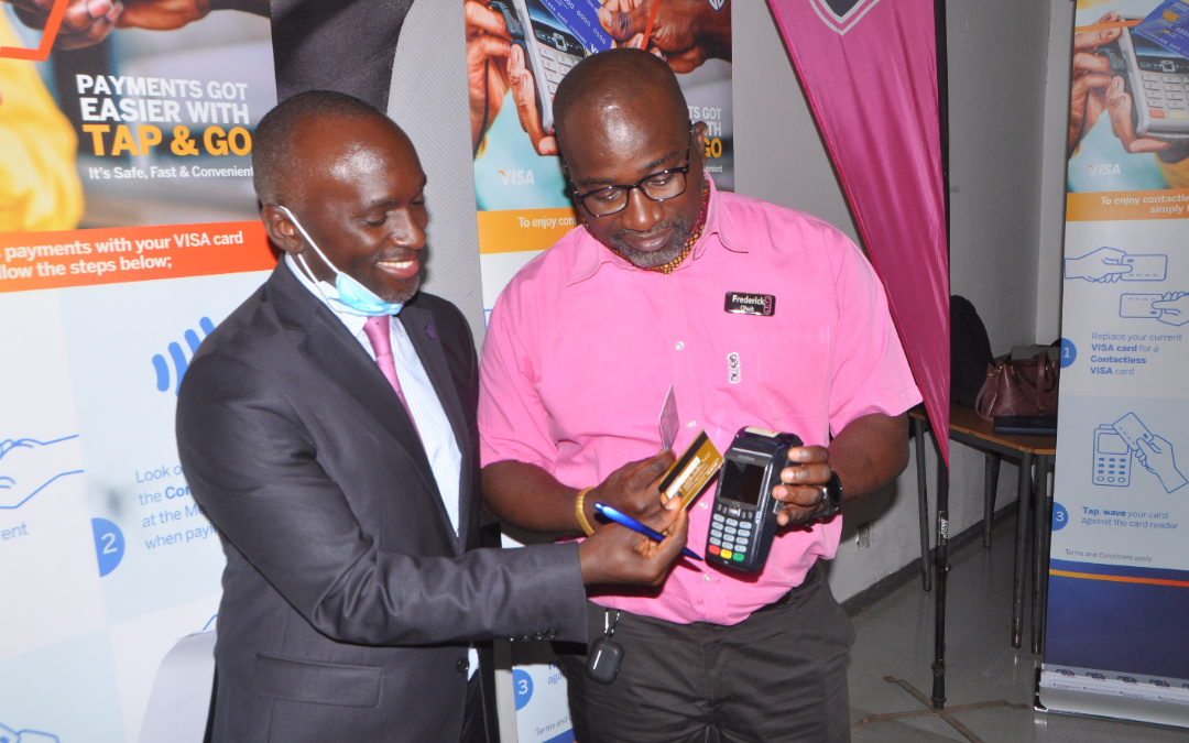 Mr. Isreal Arinaitwe, the Stanbic Bank Head of personal banking and Fredrick Olwit, Games stores manager demonstrating how the new contactless cards works (PHOTO/Courtesy).