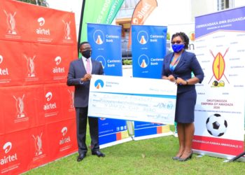 Ms. Immaculate Ngulumi the Chief Manager Marketing and Branding at Centenary Bank hands over a dummy cheque of Ugx 496 million to the Katikiiro of Buganda Charles Peter Mayiga at the launch of the 2020 Masaza Cup at Bulange Mengo (PHOTO/Courtesy).