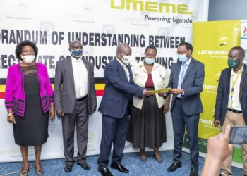 Mr. Patrick Byakatonda, the Acting Director DIT handsover over copy of the MoU to Mr Andrew Mwesigye, Head of Regional Projects at Umeme (PHOTO/Courtesy).