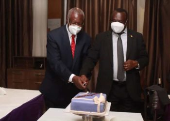 The new and former Chief Justices, Alfonse Chigamoy Owiny-Dollo (R) and Bart M. Katureebe cutting a cake (PHOTO/Courtesy).