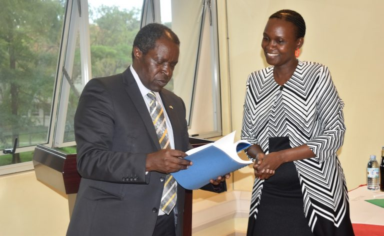 Outgoing DVCFA-Prof. WiIliam Bazeyo (L) prepares to handover a copy of his report to Dr. Josephine Nabukenya (R) during the ceremony (PHOTO/Courtesy).