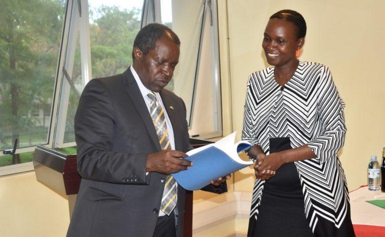 Outgoing DVCFA-Prof. WiIliam Bazeyo (L) prepares to handover a copy of his report to Dr. Josephine Nabukenya (R) during the ceremony (PHOTO/Courtesy).