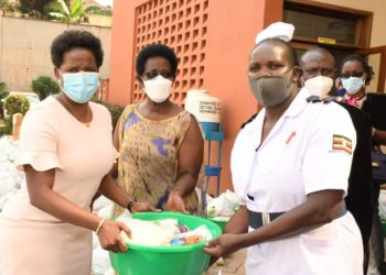 L-R: Ms Anne Juuko Chief Executive Officer of Stanbic Bank , Permanent Secretary Ministry of Health Dr Diana Atwine handing over a Christmas gift hamper to a nurse at Kawempe Referral hospital (PHOTO/Courtesy).