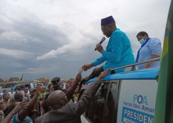 Presidential candidate Patrick Amuriat seated on top of his car campaigning (PHOTO/Courtesy).