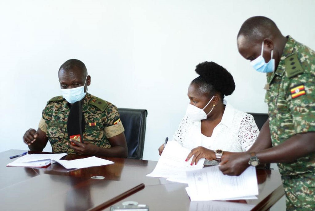 Sylvia Owori (middle) signing a contract as the new director of operations at Operation Wealth Creation (PHOTO/Courtesy).