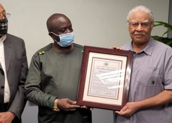 Mr. Al Washington hands over the certificate to Amb. Abby Walusimbi who represented President Museveni (PHOTO/Courtesy).