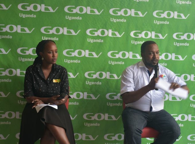 Head of Marketing at MultiChoice Uganda, Colin Asiimwe (R) speaking to the press during the launch of the Closer Together campaign at the MultiChoice Uganda offices in Kololo on Wednesday. Left is Joan Semanda Kizza, the PR and Communications Manager at MultiChoice Uganda.