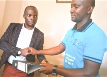 Late Robert Kagolo (R) hands over UJA office files to Bashir Mbaziira Kazibwe – MP-elect Kawempe South (L,) who has since passed over the mandate to Mathias Rukundo (not in picture.) (PHOTO/Courtesy)