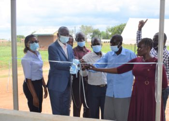 L-R: George Arodi (2L), Business Head, Uganda Baati Limited, Macklean Kukundakwe (L), Marketing Manager, Uganda Baati Limited, staff and community members at Agago Health Centre III cut a ribbon to officially open the renovated health centre III ward in Agago district (PHOTO /Courtesy).