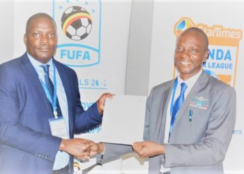 Yusuf Awuye (R) receives a document from Humphrey Mandu - the Fufa Deputy CEO. Awuye is one of the few traditional but knowledgeable football administrators in the country. (PHOTO/Courtesy)