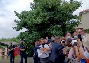 French President Emmanuel Macron is protected by a security member after getting slapped by a member of the public during a visit in Tain-L'Hermitage, France. (PHOTO/Internet)