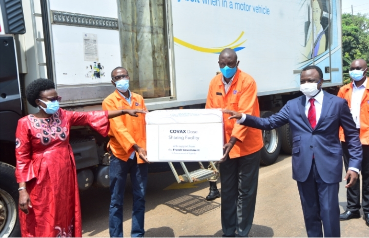 The Minister of Health - Designate, Dr. Jane Ruth Aceng (Left) receives a COVAX consignment of 175,200 AstraZeneca doses from the French Ambassador to Uganda, His Excellency Jules-Armand Aniambossou, with the help of staff (centre) of National Medical Stores (NMS), at the NMS Offices in Entebbe, Uganda on June 17th, 2021 (PHOTO /Courtesy)