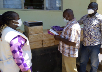 UNFPA's Patricia Nangiro left and Emmanuel Oketch at the handover of integrated HMIS tools at Abim Hospital (PHOTO/David Mafabi).